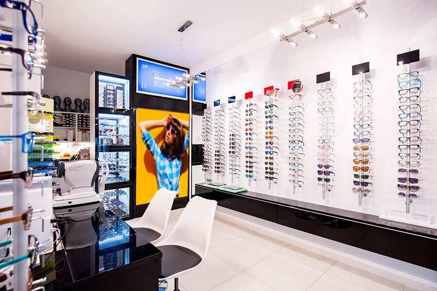 Cartel Ópticas chica con gafas de sol fondo amarillo   Carteles XXL - Impresión carteleria publicitaria